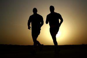 Silhouetten von zwei Läufern in der Abenddämmerung