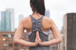 Junge Frau macht Yoga Übung, führt Hände am Rücken zusammen