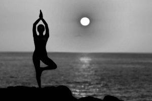 Silhouette von junger Frau, die Yoga am Meer übt, im Sonnenuntergang
