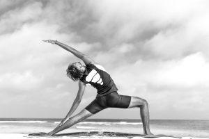 Yogi am Strand von Bali, hinter ihm das blaue Meer, junger Mann übt Yoga