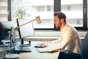 Mann arbeitet im Büro, fröhlich lachend