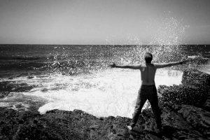 Mann am Meer, Arme ausgebreitet, genießt die Wellen an den Klippen