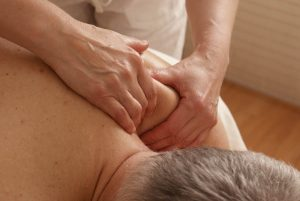 Hände in Nahaufnahme, die eine Massage am Patienten durchführen