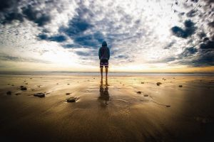 Junger Mann in Trainingskleidung schaut aufs Meer, Wolkenhimmel