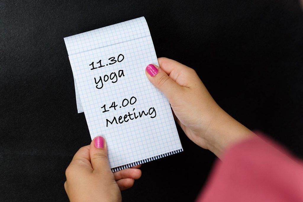 Junge Frau hält Notizblock mit Yogatermin