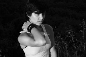 Sportlerin fasst sich an schmerzenden Nacken