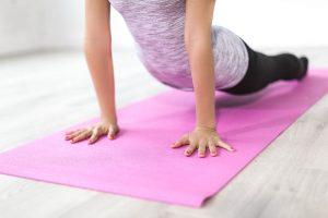 Frau auf Matte macht Yoga