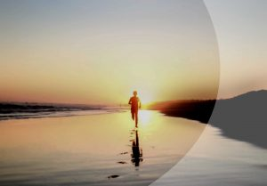 Einzelne Person läuft am Strand im Sonnenunetrgang