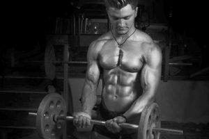 Ernährungsziel Muskelaufbau: Junger Mann mit muskulösem Oberkörper stemmt Hantel