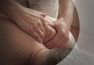 Massage-Behandlung am Schultermuskel, Hände in Nahaufnahme