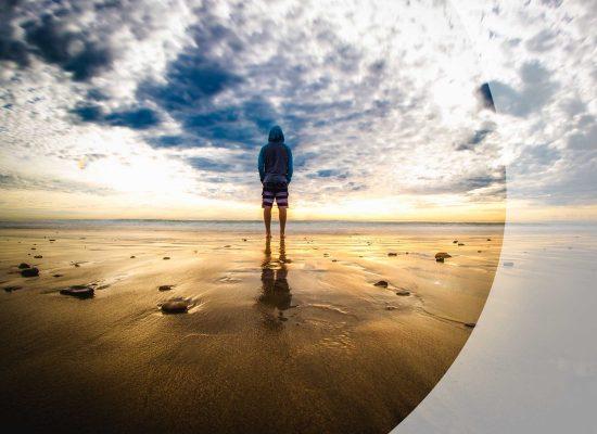 Mann von hinten, schaut aufs Meer, stimmungsvoller Wolkenhimmel