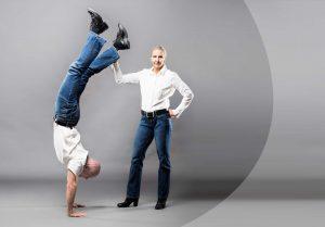 Susanne und Christian, weiße Hemden und Jeans tragend, Christian im Handstand