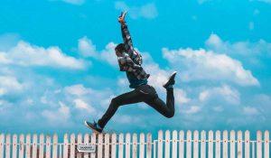 Junger Mann, Silhouette, Springt über Zaun