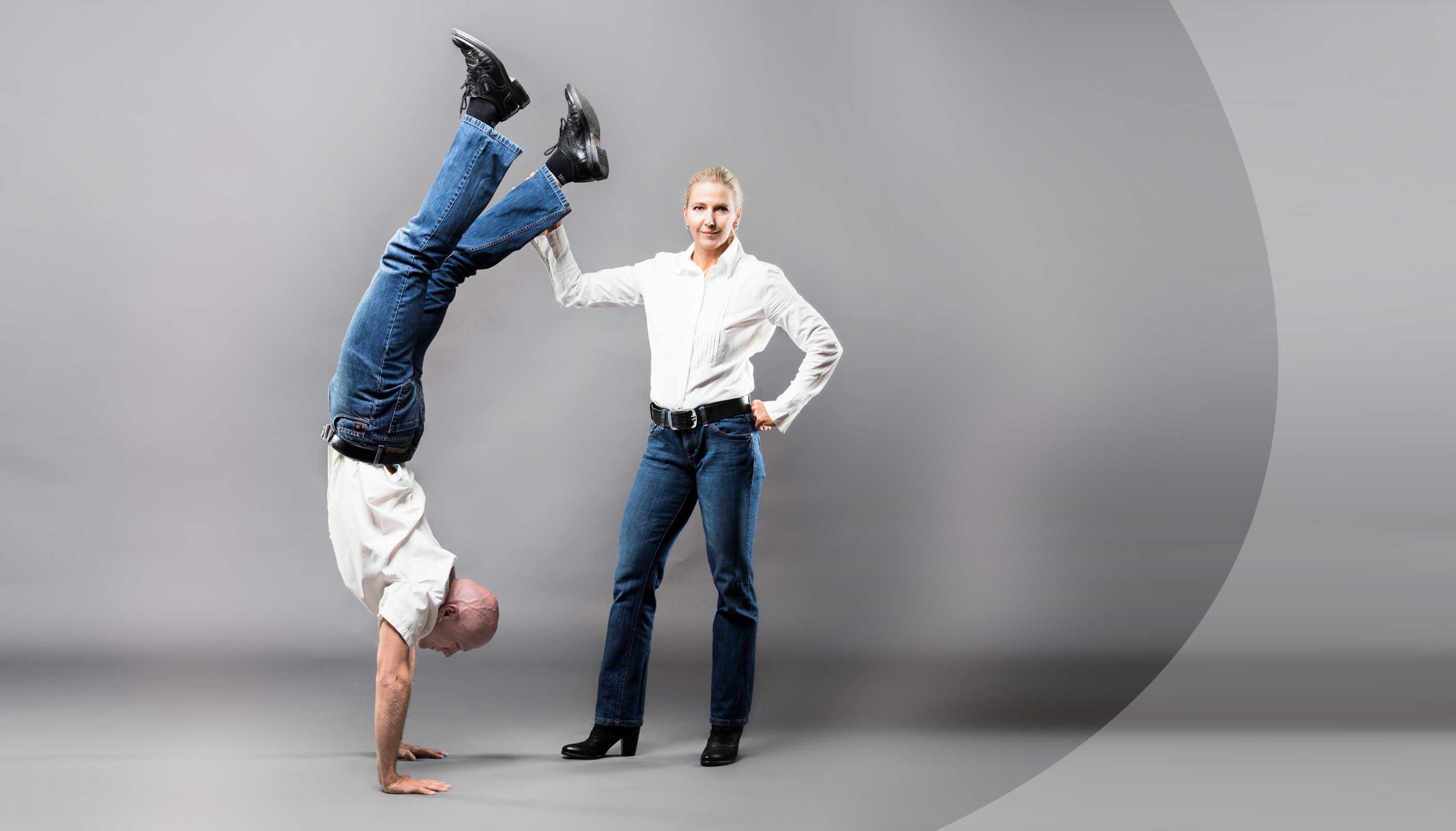 Susanne und Christian in Jeans und weißem Hemd, Christian im Handstand