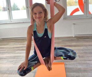 Aerial Yoga, Kinderkurse, Mädchen hängend in der Luft im Aerial Yoga Tuch, lacht