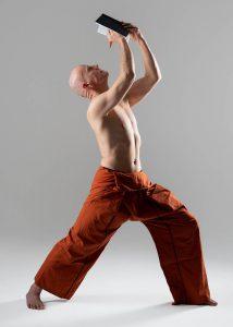 Christian Bechtel in Yoga-Haltung Krieger schreibt gleichzeitig in Notizbuch