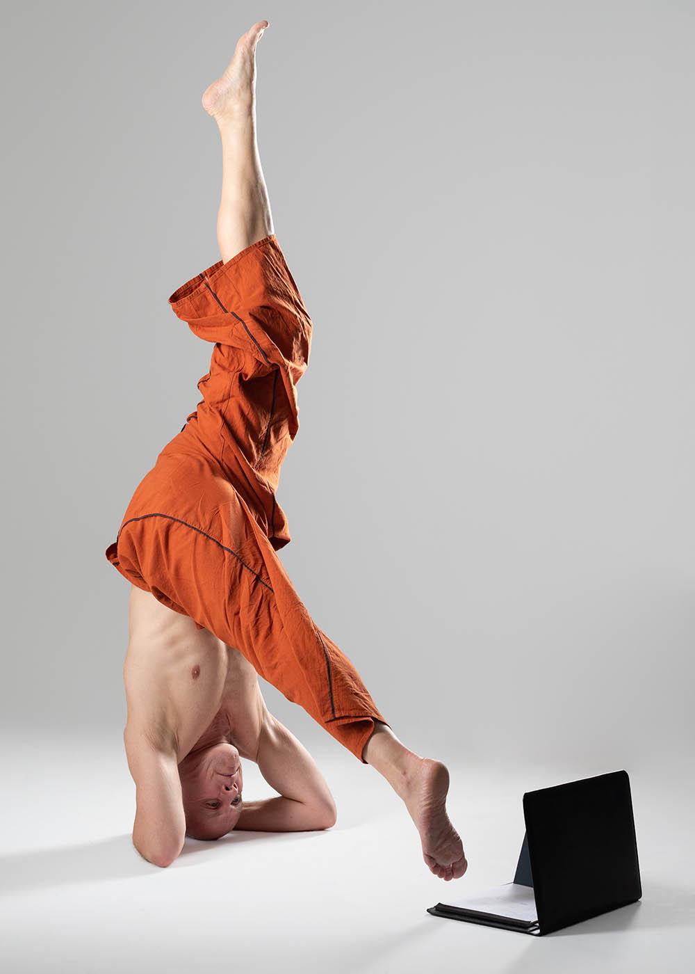Christian Bechtel macht Handstand vor Laptop