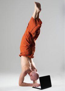 Christian Bechtel macht Handstand und tippt gleichtzeitig auf Laptop
